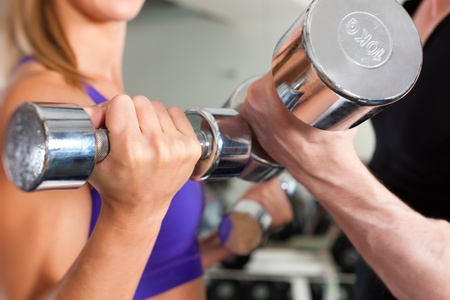pectoral: Young couple - man and woman - is exercising with barbell in gym to strengthen the muscles