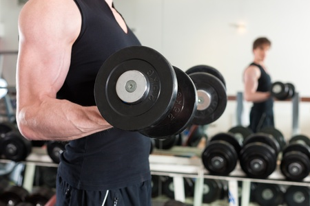 pectoral: Young man is exercising with barbell in gym to strengthen the muscles