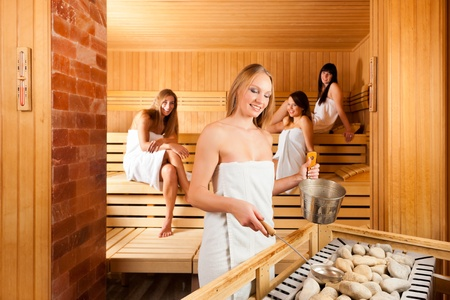 Wellness - four young happy women in sauna of a Spa, water and scent are splashed on hot stones for steam photo