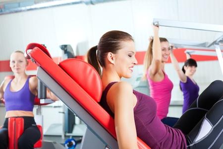 Vier junge Frauen, die St�rke oder sportliches Training in der Turnhalle f�r eine bessere Fitness