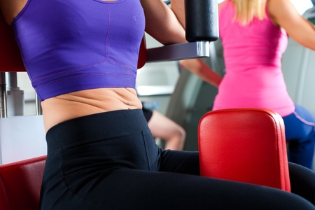 Three young women doing strength or sports training in gym for a better fitness; close-up photo