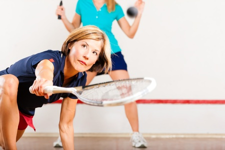 racket sport: Dos mujeres que juegan al squash, deporte de raqueta en el gimnasio, puede que sea una competencia Foto de archivo