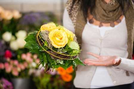 Female florist in flower shop or nursery presenting her plants on display photo