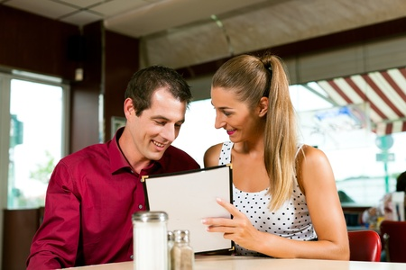 dinner date: Happy couple is ordering lunch or dinner in a bar or restaurant