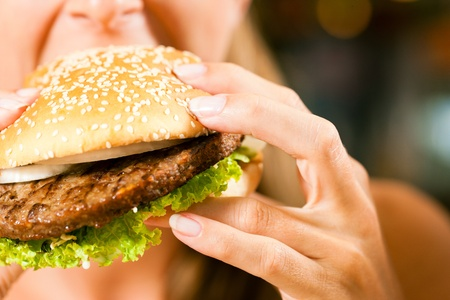 unhealthy: Happy woman in a restaurant eating a fast food hamburger and seems to enjoy it