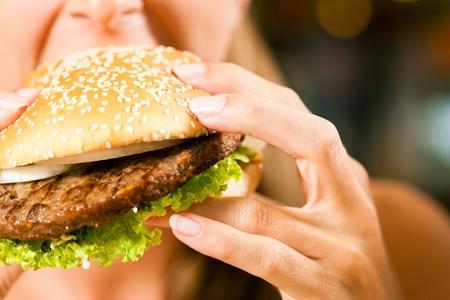 comida chatarra: Mujer feliz en un restaurante comiendo una hamburguesa de comida rápida y parece que lo disfruta