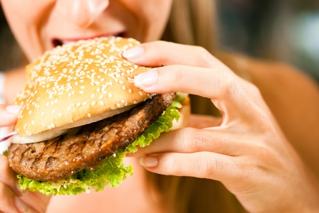 Happy woman in a restaurant eating a fast food hamburger and seems to enjoy it