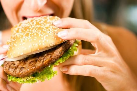 Glückliche Frau in einem Restaurant essen eine Fast-Food-Hamburger und scheint es zu geniessen