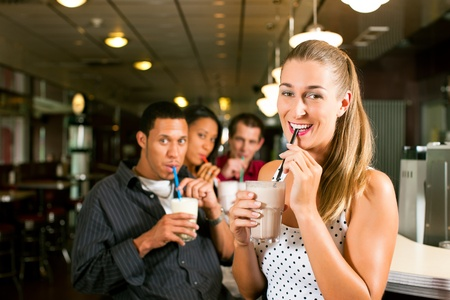 Friends drinking milkshakes in a bar and have lots of fun; focus on the woman in front Stock Photo - 11840642
