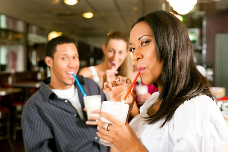 Friends drinking milkshakes in a bar and have lots of fun; focus on the woman in front photo