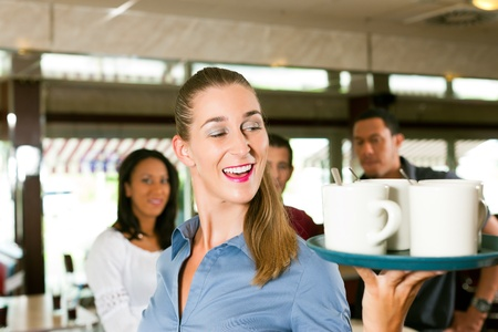 Woman as waitress in a bar or restaurant with coffee mugs; in the background are guests photo