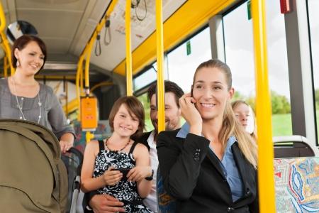 passenger vehicle: Los pasajeros de un autob�s, un viajero, una mujer con un cochecito, un hombre Foto de archivo