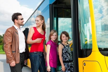 passenger vehicle: Los pasajeros que abordan un autob�s en una estaci�n de autobuses Foto de archivo