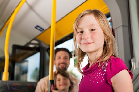 Child in a bus; in the background presumably her father and sister to be seen photo
