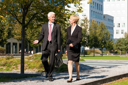 experienced: Business people - mature or senior -  talking outdoors and walking in a park Stock Photo