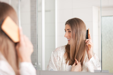 hair brush: Young woman in pyjama brushing her long dark-blond hair after getting up in the morning