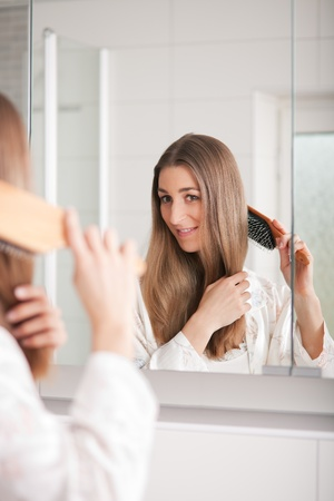 pyjama: Young woman in pyjama brushing her long dark-blond hair after getting up in the morning