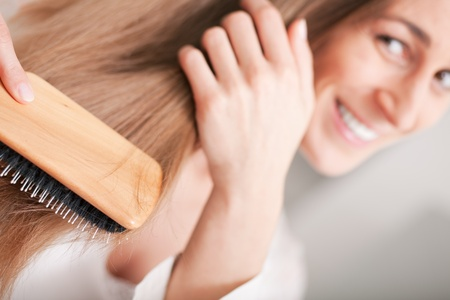 combing hair: Young woman in pyjama brushing her long dark-blond hair after getting up in the morning