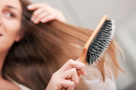 Giovane donna spazzolatura sua lunga capelli biondo scuro dopo essersi alzati al mattino; attenzione pennello!