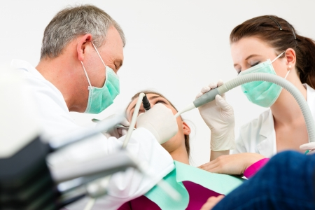 male dentist: Female patient with dentist and assistant in a dental treatment, wearing masks and gloves, Dentist and assistant bowing over her using sucker and drill