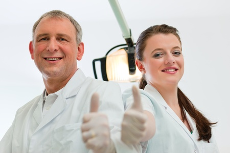Dentists in their surgery looking at the viewer standing side by side photo