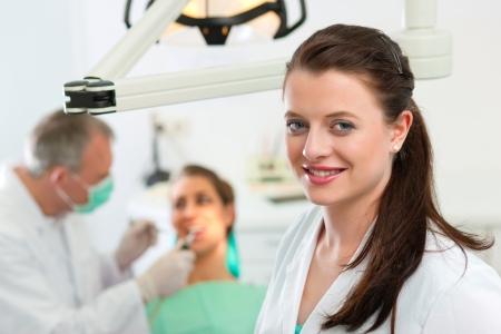 Zahn�rzte in ihrer Operation Blick auf den Betrachter, im Hintergrund ist ihr Kollege gibt einer Patientin eine Behandlung