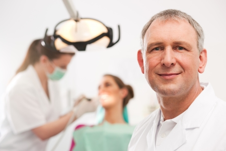 male dentist: Dentists in his surgery looking at the viewer, in the background his assistant is giving a female patient a treatment  Stock Photo