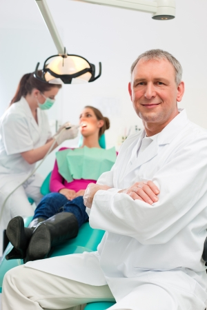 dental nurse: Dentists in his surgery looking at the viewer, in the background his assistant is giving a female patient a treatment  Stock Photo