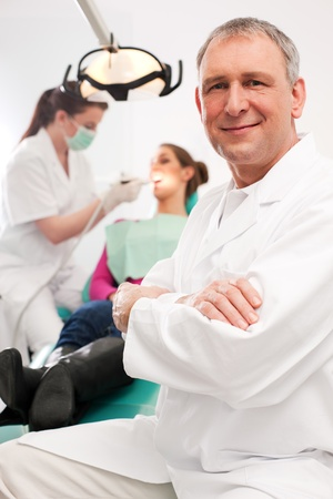 Dentists in his surgery looking at the viewer, in the background his assistant is giving a female patient a treatment  photo