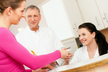 reception office: Patient in reception area of office of doctor or dentist, handing her health insurance card over the counter to the nurse, the doctor standing in the background and is writing things on a clipboard  Stock Photo