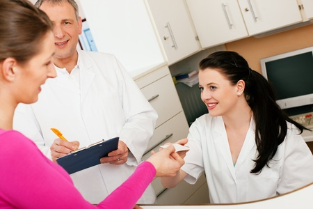standing reception: Patient in reception area of office of doctor or dentist, handing her health insurance card over the counter to the nurse, the doctor standing in the background and is writing things on a clipboard  Stock Photo