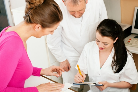 health insurance: Patient in reception area of office of doctor or dentist, handing her health insurance card over the counter to the nurse who is writing things on a clipboard, the doctor standing in the background