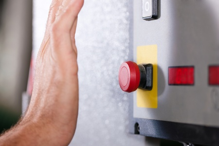 panic button: Man is shutting off a machine with the emergency button - probably in a case of danger