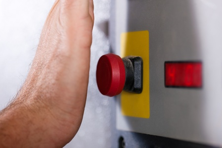 Man is shutting off a machine with the emergency button - probably in a case of danger