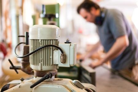 planos electricos: Carpenter est� de pie en la cortadora el�ctrica de poner el componente en el - Enfoque en el motor de la cortadora