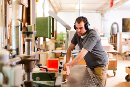 carpintero: Carpenter est� de pie en la cortadora el�ctrica con protecci�n para los o�dos