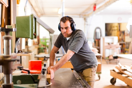 Carpenter is standing on electric cutter with ear protection  photo