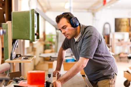 Carpenter is standing on electric cutter with ear protection Stock Photo - 11912132
