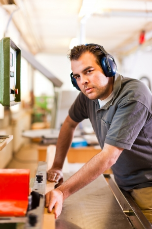 workplace safety: Carpenter is standing on electric cutter with ear protection  Stock Photo