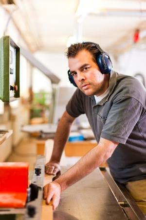 Timmerman staat op elektrische frees met gehoorbescherming