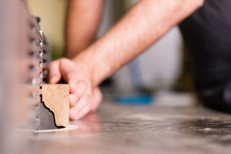 Timmerman - alleen handen te zien - staat op elektrische doorslijpmachine; close-up op het onderdeel