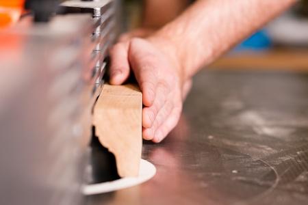 planos electricos: Carpenter - �nicas manos para ser visto - est� de pie sobre cortador de el�ctrica; cerca de para arriba en la parte componente Foto de archivo