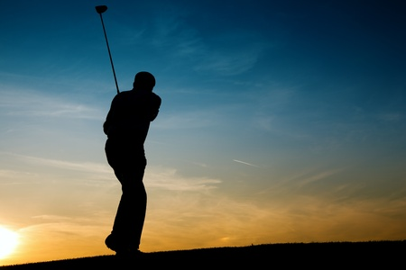Senior man playing golf - pictured as a silhouette against an evening sky photo