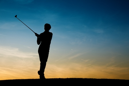 Senior woman playing golf - pictured as a silhouette against an evening sky photo