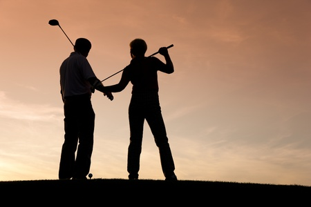 Mature or senior couple playing golf - pictured as a silhouette against an evening sky Stock Photo - 11911763