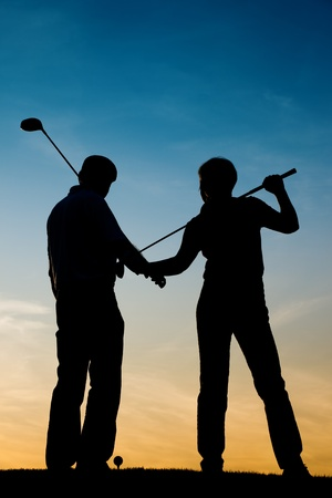 woman golf: Mature or senior couple playing golf - pictured as a silhouette against an evening sky