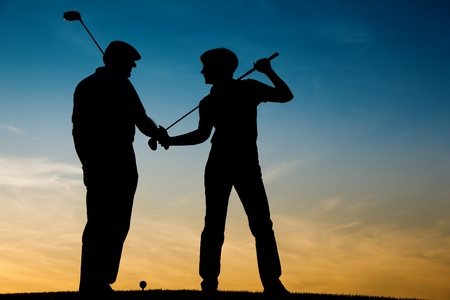 golfers: Mature or senior couple playing golf - pictured as a silhouette against an evening sky