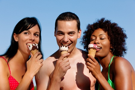 eating ice cream: Gruppo di amici - un uomo e due donne, mangiare il gelato in costume da bagno e bikini, sembra essere una calda giornata estiva