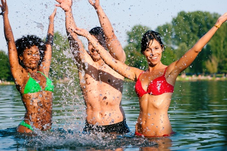 Group of friends - man and to women stretching arms in the water of a lake on a hot summer day Stock Photo - 11912644