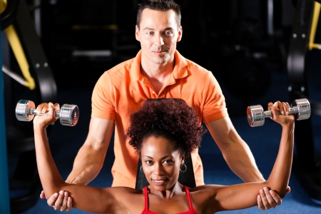 coach sport: Woman with her personal fitness trainer in the gym exercising with dumbbells